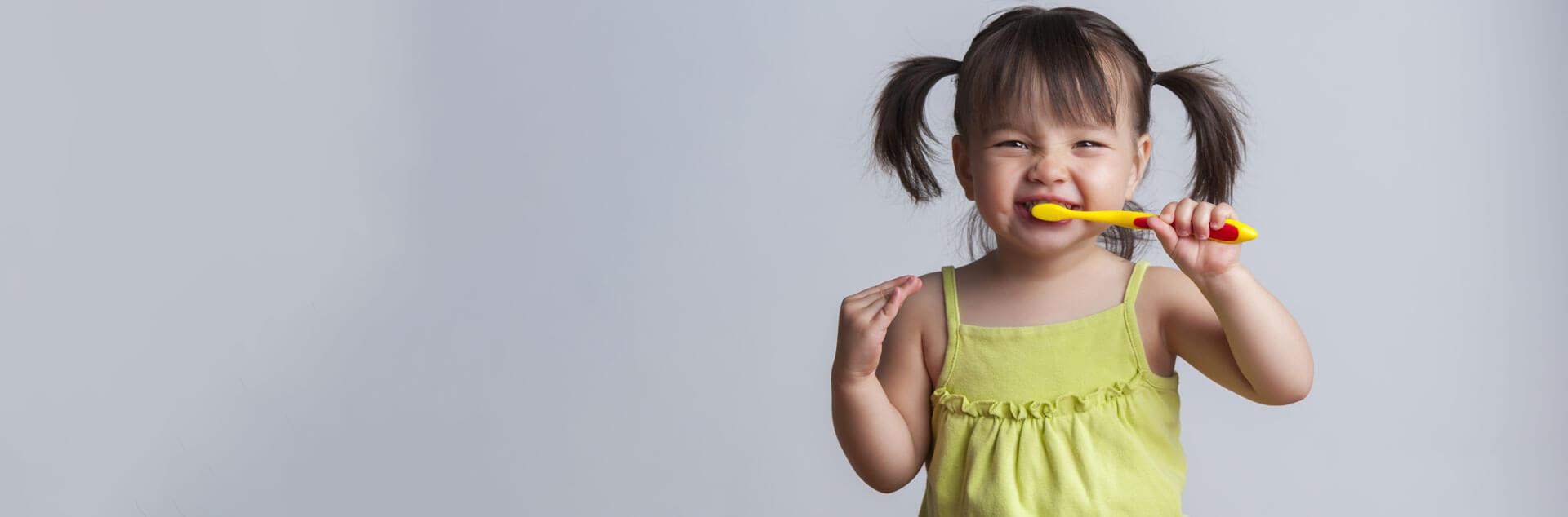 Little girl brushing her teeth in grey background
