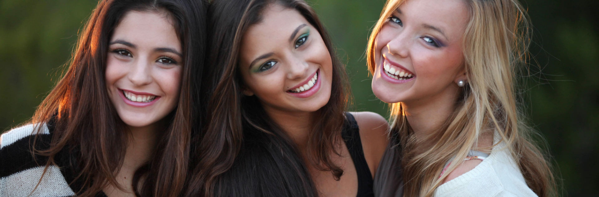 3 beautiful young women smiling beautifully as a result of cosmetic dentistry
