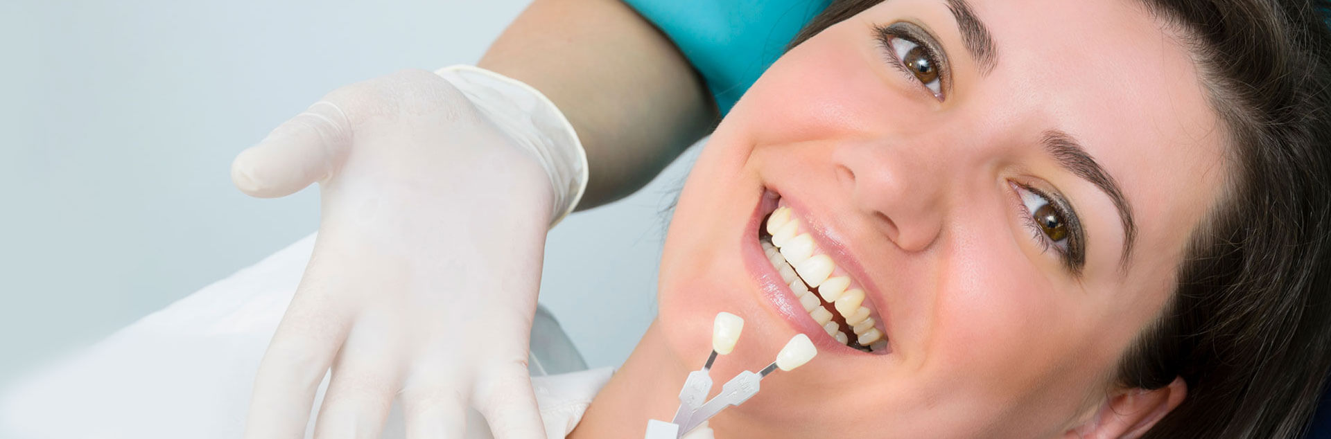 Female patient smiling while comparing her teeth with pair of dental crowns