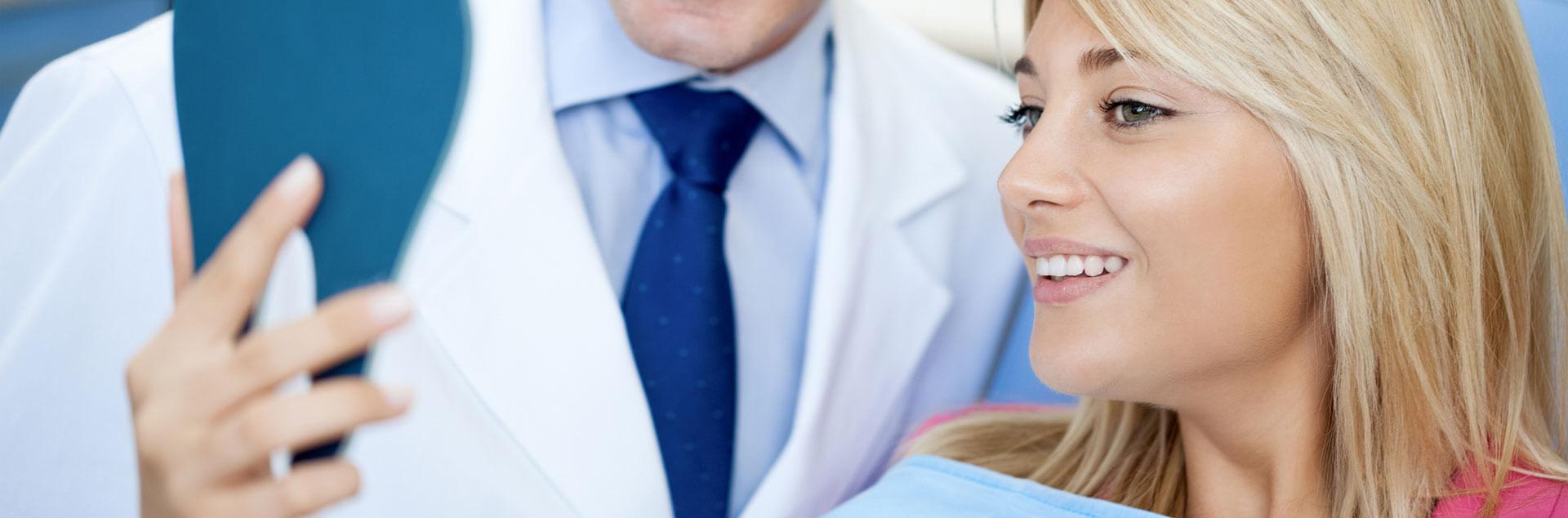 Female patient checking her smile after dental restoration