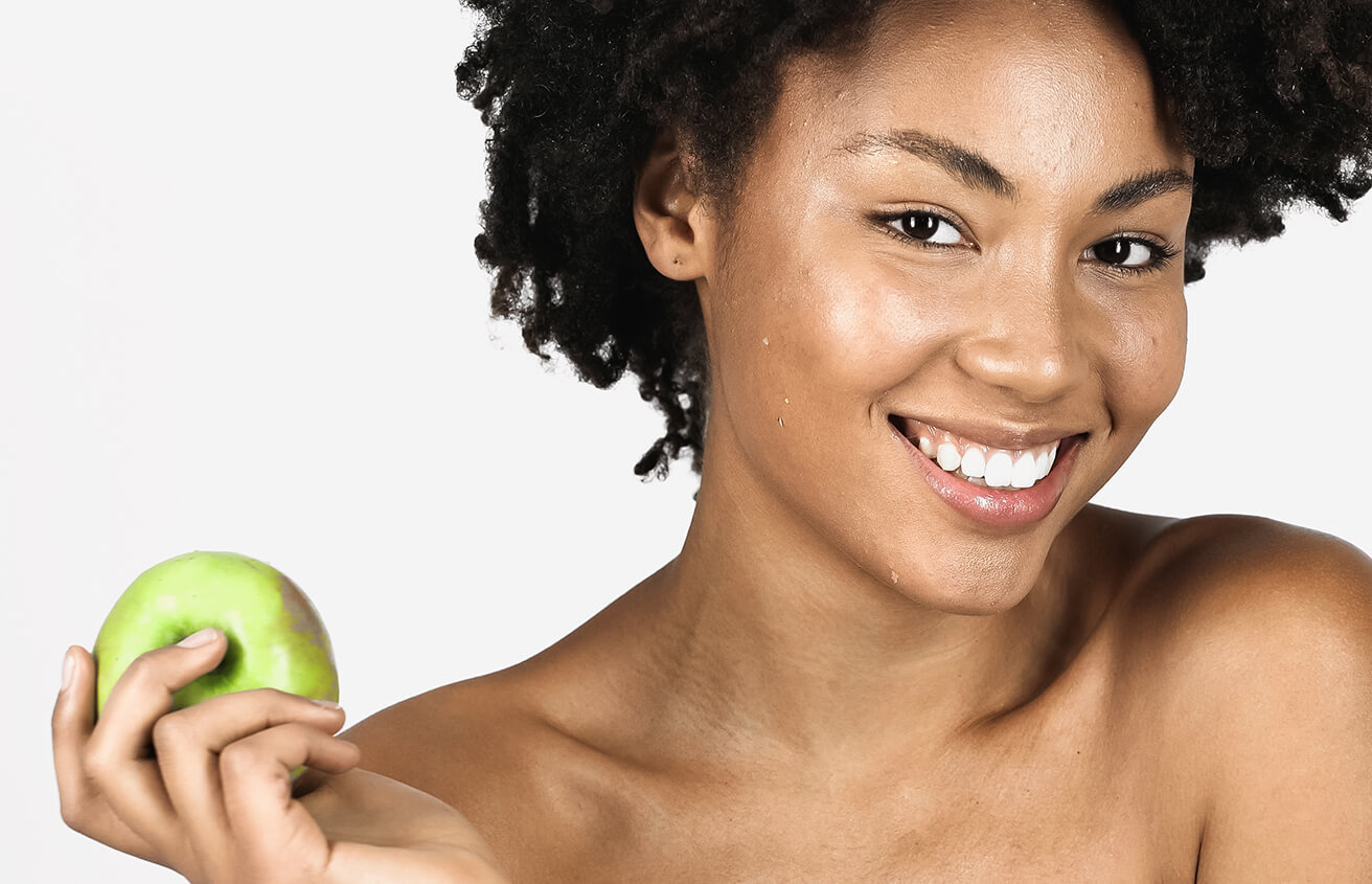 Smiling Young Woman Holding an Apple