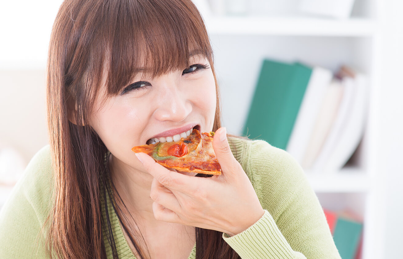 Pretty Girl Eating a Slice of Pizza