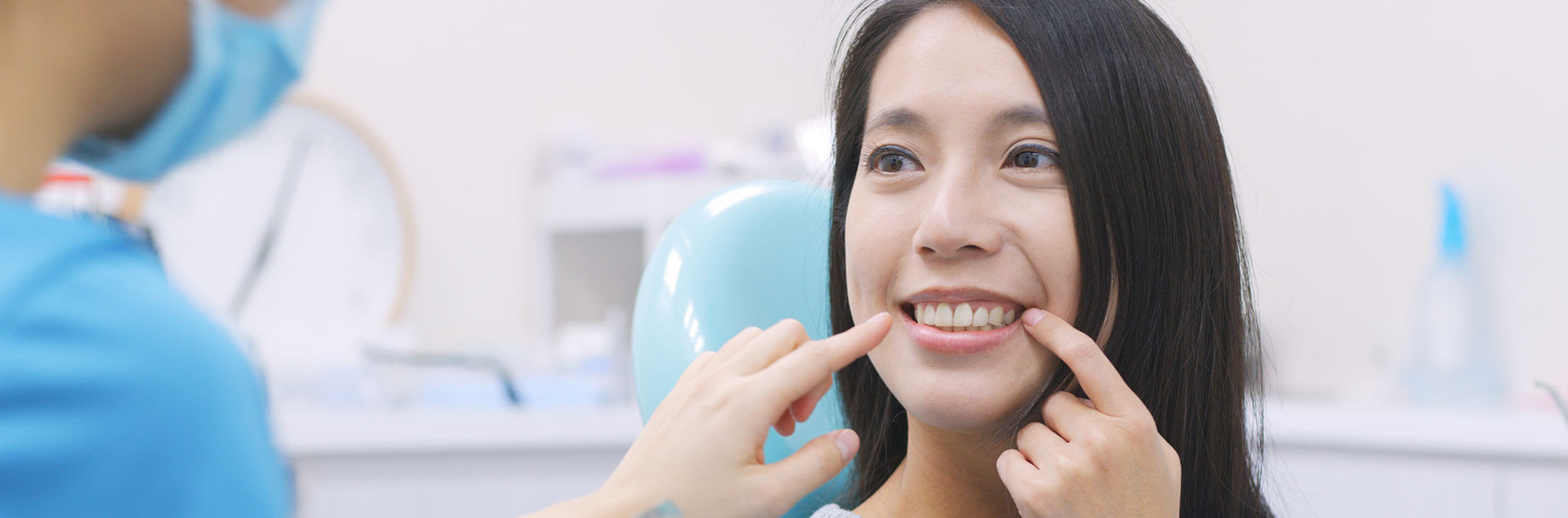 Young female patient pointing at her dental implants