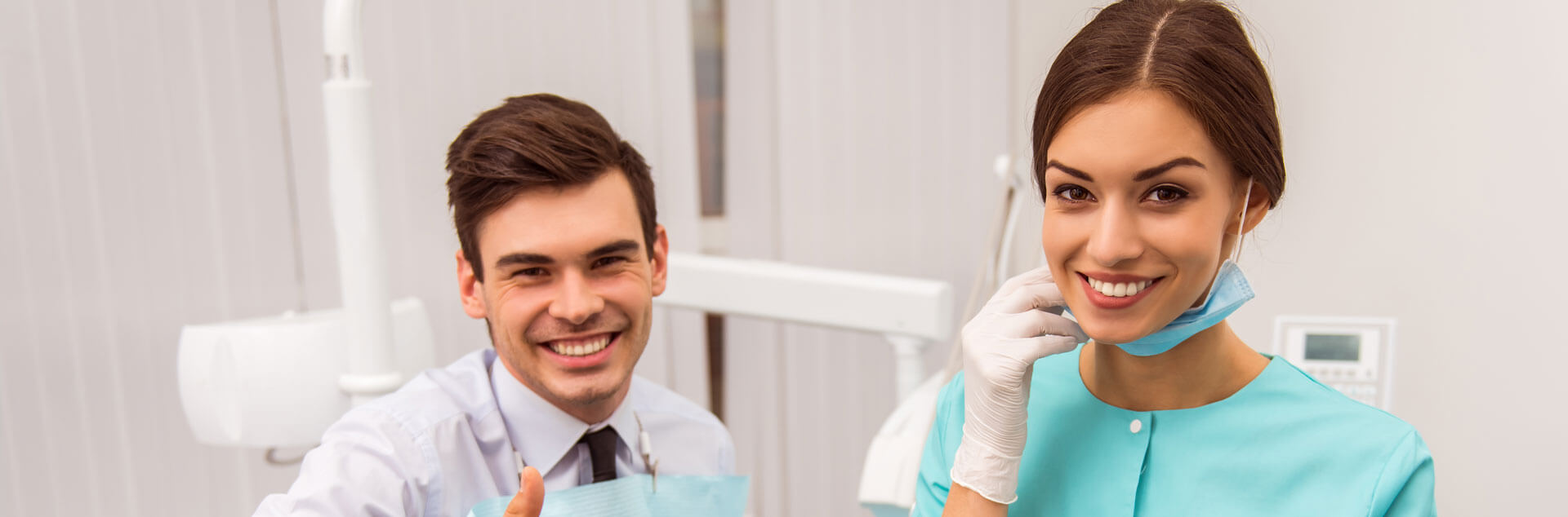 Male patient and female dental assistant smiling at the camera