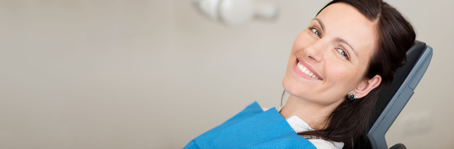 smiling female patient seated on dental chair after receiving multiple teeth replacement