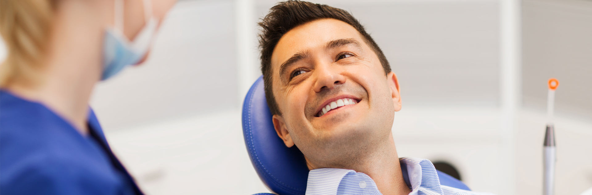 Young male patient smiling seated on dental chair about to receive preventative dentistry treatment