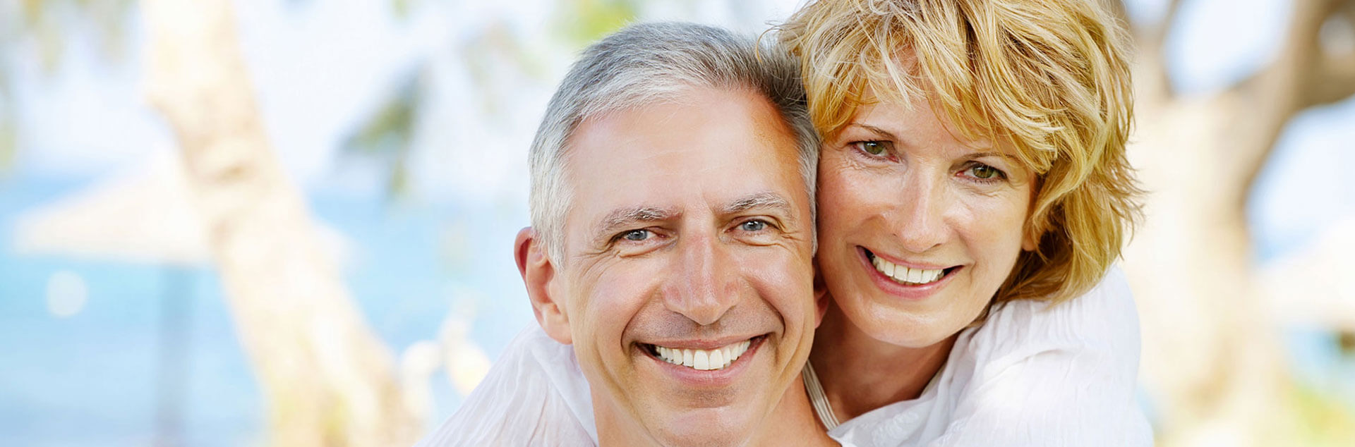 Elderly couple embracing each other and smiling at the camera after root canal treatment