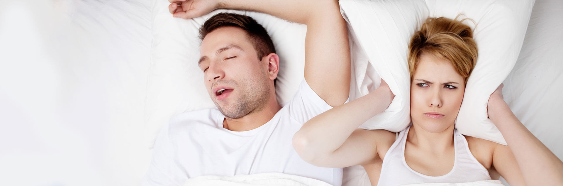 Couple sleeping while female is unhappy due to sleep apnea snoring of the male