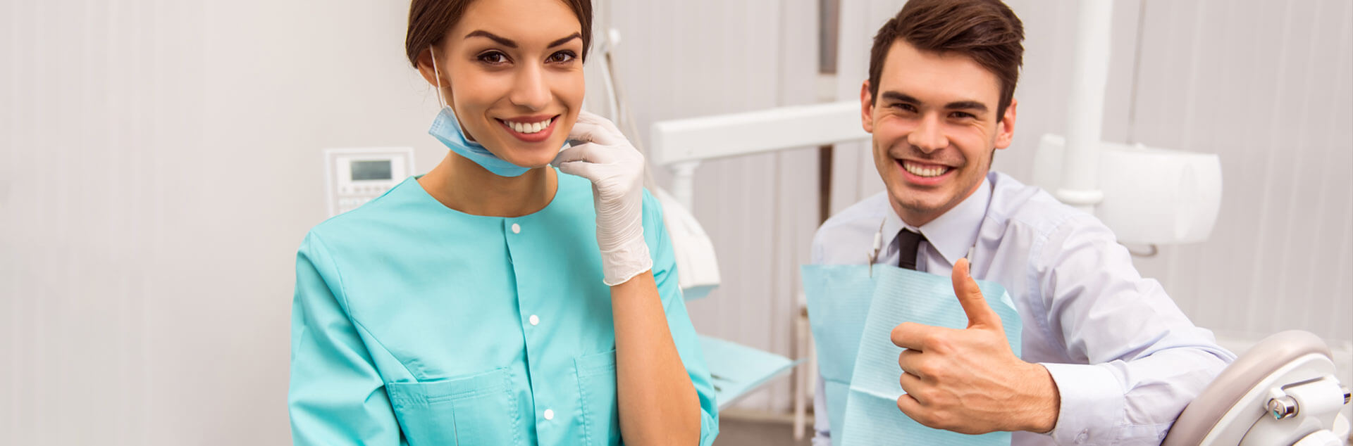 Dental assistant smiling and patient smiling while showing thumbs up
